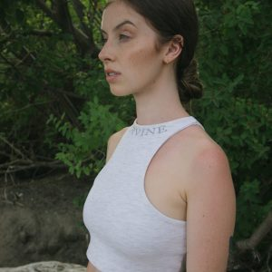 model is wearing our reverse racer crop top in the color heather grey